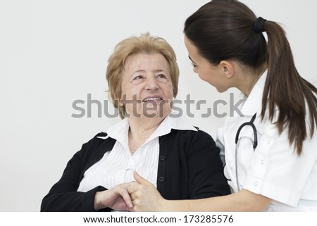 Young nurse and female senior patient looking at each other. - stock photo