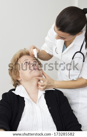 Young nurse applying eye drops  her female senior women. - stock photo