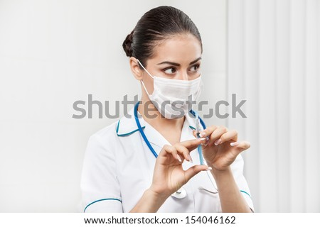 young nurse - beautiful brunette woman medical worker wearing protective mask