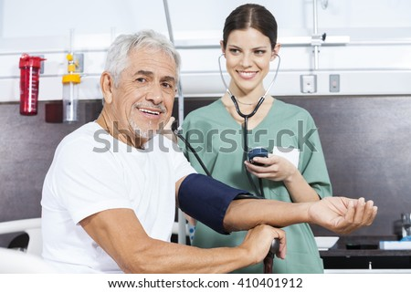 Young Nurse Checking Blood Pressure Of Senior Patient - stock photo
