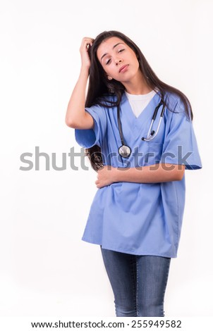 young nurse dressed in blue with stethoscope on her neck running her hand through her hair