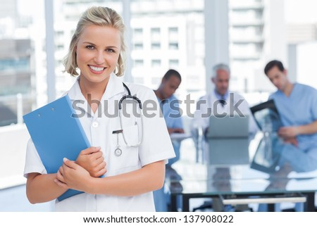 Young nurse holding file in office