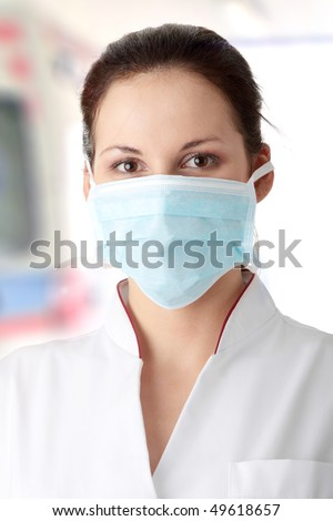 Young nurse in mask , with ambulance in background - stock photo