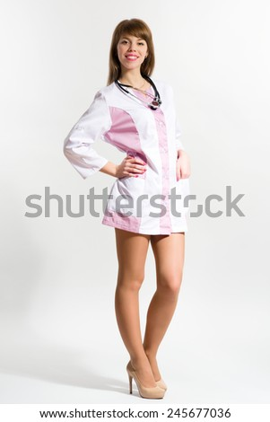 Young nurse in short medical gown with stethoscope standing against grey background - stock photo