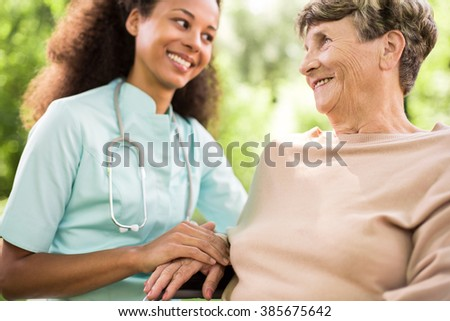 Young nurse is holding elder woman's hand  - stock photo