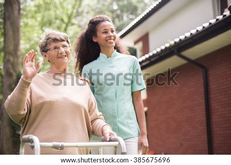 Young nurse is strolling with elder woman