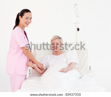 Young Nurse measuring an elderly patients Pulse - stock photo