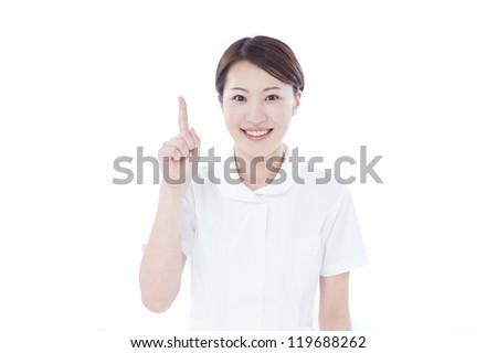 Young nurse pointing copy space, isolated on white background - stock photo