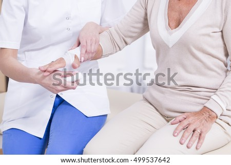 Young nurse putting the bandage on elder woman's hand