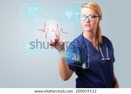 Young nurse standing and pressing modern medical type of buttons