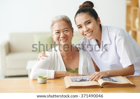 Young nurse taking care of aged female in clinic - stock photo