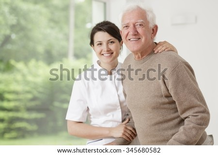 Young nurse taking care of old sick man - stock photo