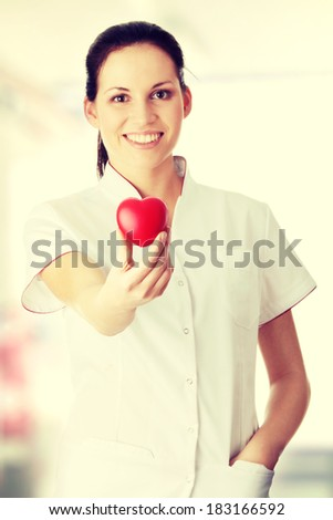 Young nurse with heart in her hand - stock photo