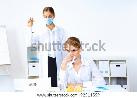 Young nurse with syringe doing vaccination in office - stock photo