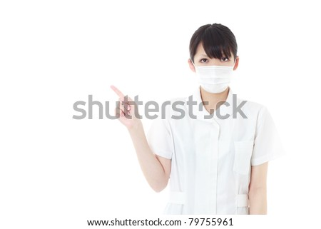 Young nurse woman pointing at white background