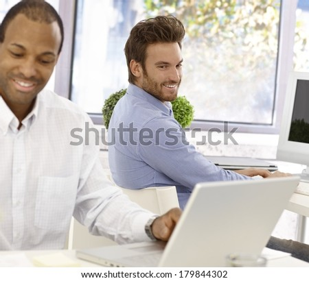 Young office worker peeping his colleagues screen, smiling. - stock photo