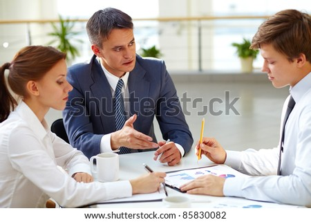 Young office worker reporting to his boss about work - stock photo