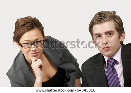 Young office workers listening with serious expression - stock photo