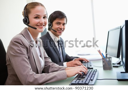 Young office workers using computers in an office - stock photo