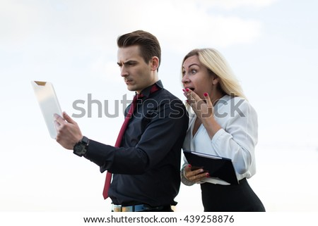 Young office workers with tablets on the background of the city woman surprised  - stock photo