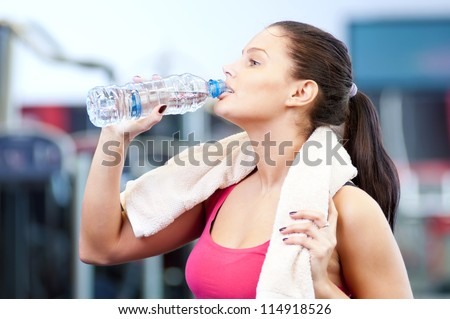 Young oman drinking water after sports. Fitness gym. - stock photo