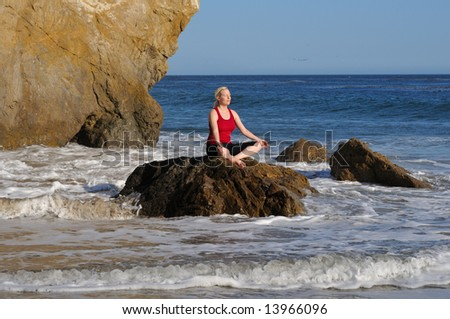 Young oman performs yoga meditation on a rock in the surf, facing the sun.