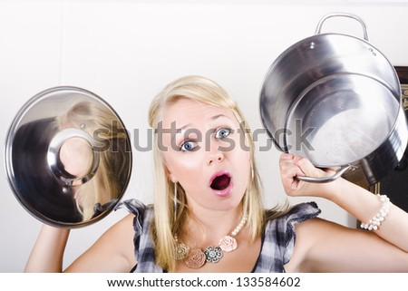 Young open-mouthed blond woman holding empty pot and lid with surprise expression