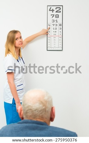 Young optician showing the numbers on the typescript for elderly patient. - stock photo