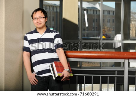 Young Oriental Man holding his books with college campus as background