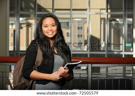 Young Oriental Woman Student holding a copybook inside a college campus - stock photo