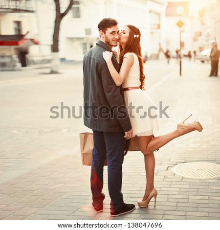 Young outdoor fashion portrait of beautiful couple kissing on the street - stock photo