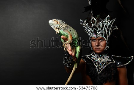 Young pagan priest in ritual suit with green iguana in his hands. Photo. - stock photo