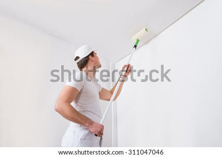 Young Painter In White Uniform Painting With Paint Roller On Wall - stock photo