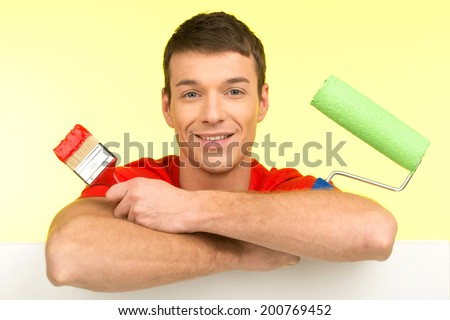 young painter sitting holding painting tools. man with painting brush and roller smiling - stock photo
