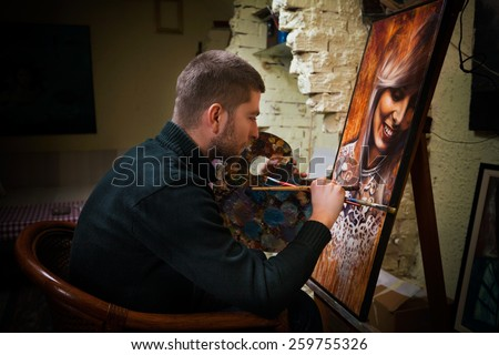 Young painter working on oil painting portrait in his art studio. - stock photo