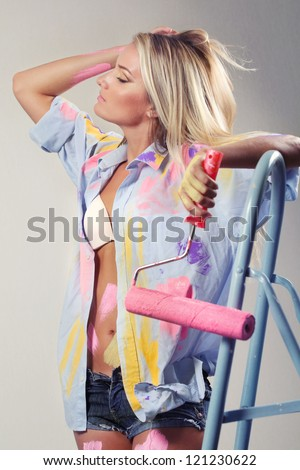 Young painting  woman with rollers sitting on step-ladder