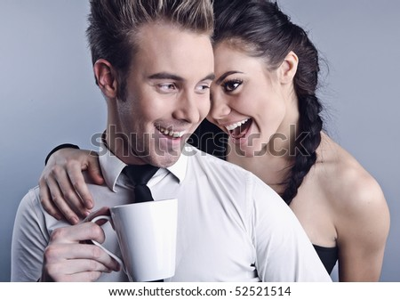 Young pair acquaintance. He holds a mug in his hands, she shows liking. Photo. - stock photo
