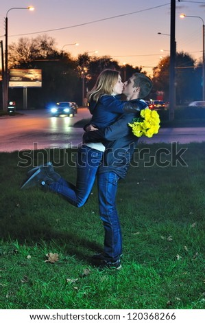 young pair kisses in the evening near the road - stock photo