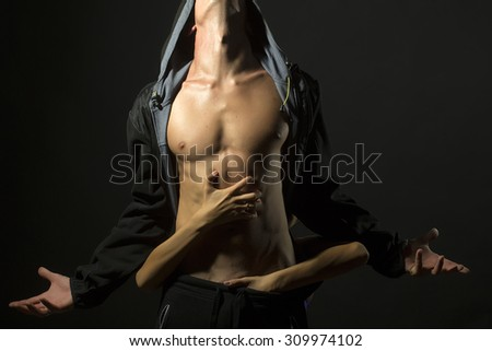 Young pair of man with sexual strong muscular body in leather jacket with hood looking up and woman embracing with hands standing on studio black background, horizontal picture - stock photo