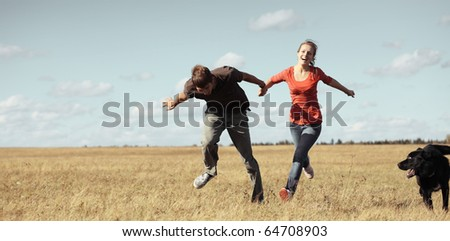 Young pair running on meadow with a dog - stock photo