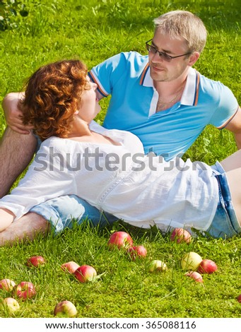 young pair sitting on a grass with apples - stock photo