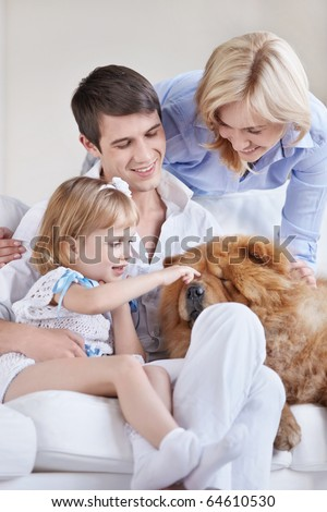 Young parents and the child playing with a dog