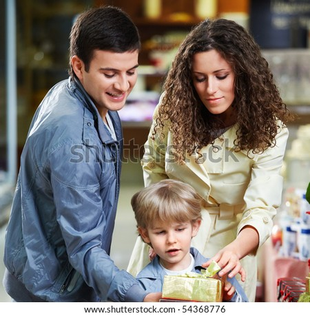 Young parents and the small son hold a gift box - stock photo