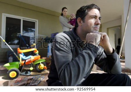 Young parents and their daughter outside their home. Concept photo illustrating divorce, homelessness, eviction, unemployment, financial, marriage problem or family issues. - stock photo