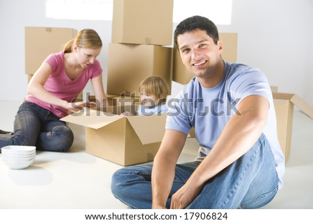 Young parents and their daughter sitting beside cardboard boxes. Young girl sitting in box. They're smiling. Focused on man who sitting in front.