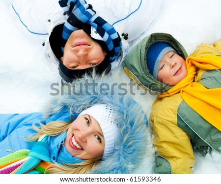 young parents and their son wearing warm winter clothes lie on the snow (focus on the mother) - stock photo