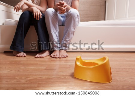 Young parents are sitting on the bed and thinking how to teach kid to use children's pot. - stock photo