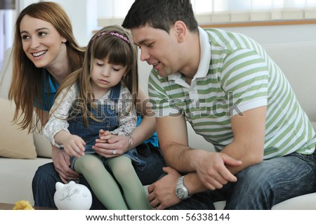 young parents at home with beautiful child make savings and put coins money in piggy bank - stock photo