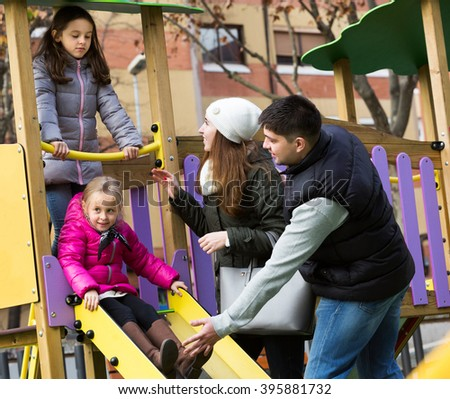 Young parents helping kids on slide in autumn day. Focus on woman - stock photo