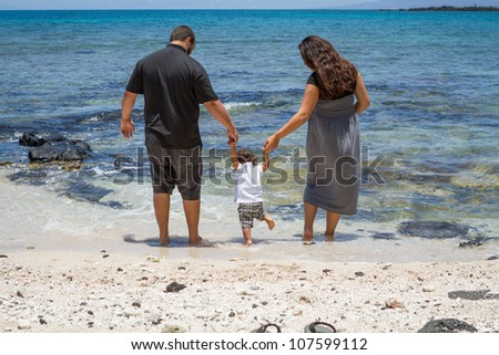 Young parents helping their toddler get his feet wet at the beach.